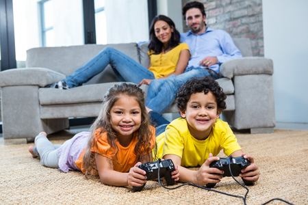 games: Children playing video games on the carpet in living room while parents on the sofa Stock Photo