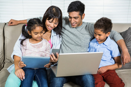 family sofa: Smiling family on the sofa using technology Stock Photo