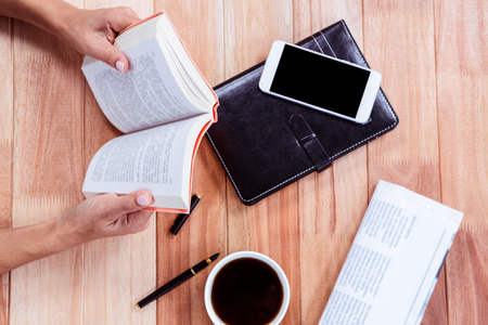 turning table: Overhead of feminine hands holding a book with coffee, agenda, newspaper and smartphone on table