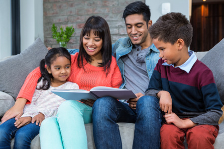 convivial: Happy young family reading a book together in living room