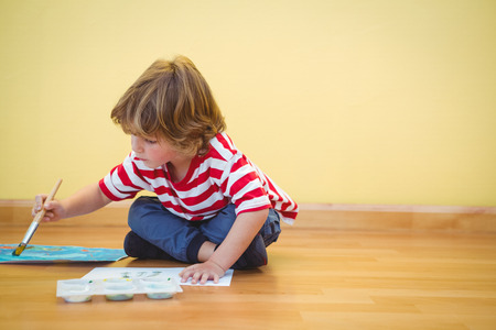sitting on the ground: Boy using a paintbrush to paint a sheet of paper