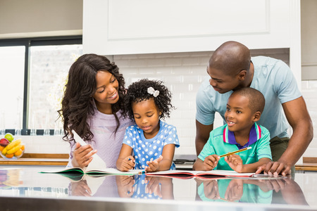 happy families: Parents helping children doing homework in the kitchen Stock Photo