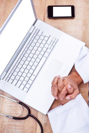 mani incrociate: Vista del medico con le mani incrociate sulla scrivania