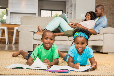family sofa: Happy siblings on the floor drawing in the living room Stock Photo