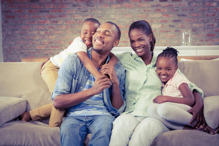 thirties portrait: Happy family relaxing on the couch in living room