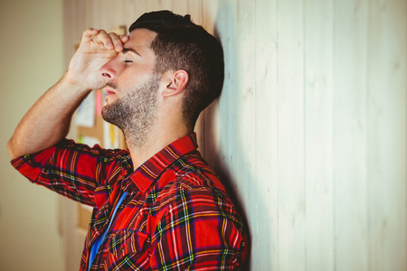 apprehensive: Handsome hipster feeling stressed out on wooden background Stock Photo