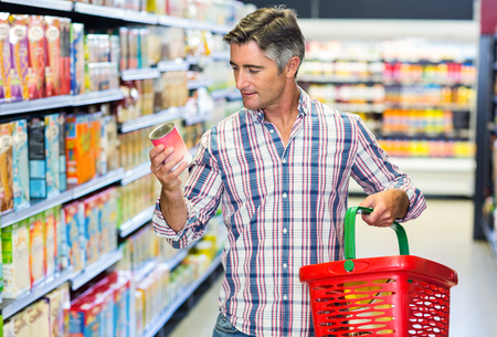 nutritional: Man reading nutritional values at supermarket Stock Photo