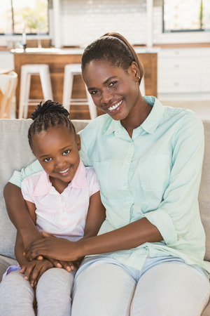 one parent: Loving mother with daughter on the couch in living room