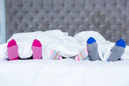 Gezin voeten met sokken steken uit de deken