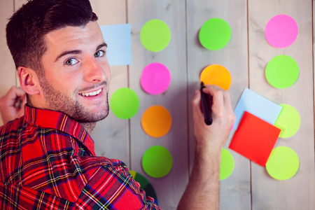 young adult men: Creative worker using wall for brainstorm in his office