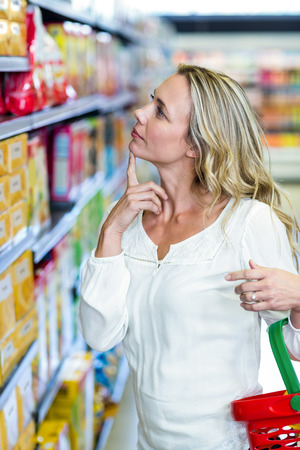 the thoughtful: Thoughtful woman looking at shelves in the supermarket Stock Photo