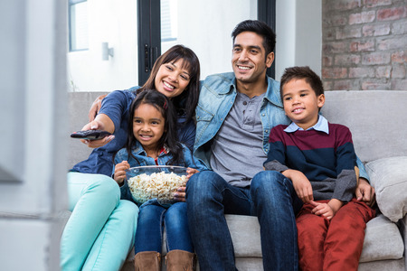 Happy young family eating popcorn while watching tv in living room Stock Photo