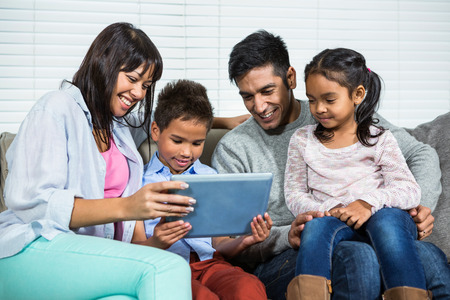 affections: Smiling family on the sofa using tablet in living room Stock Photo