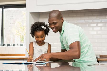 niños negros: Padre ayudando a su hija con la tarea en la cocina