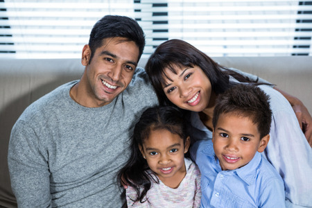 convivial: Happy young family posing together on the couch in living room Stock Photo
