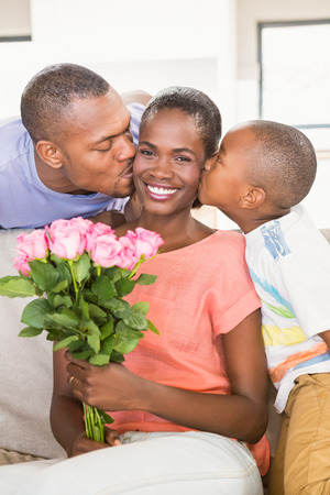 flowers boy: Son surprising mother with flowers in living room