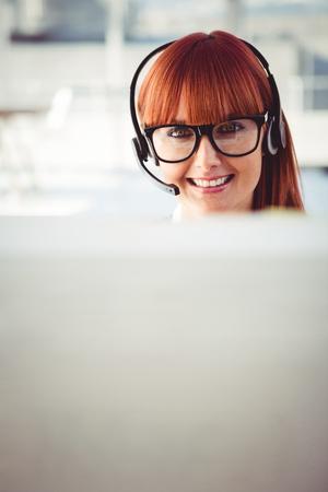 servicio al cliente: Mujer inconformista atractivo con el auricular en su oficina