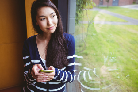 university text: Smiling student with smartphone and looking through the window at the university Stock Photo