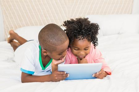 black girl: Glückliche Geschwister auf dem Bett mit dem Tablet zu Hause