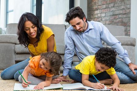 deberes: Familia sentado sobre una alfombra en la sala de estar con los niños de dibujo