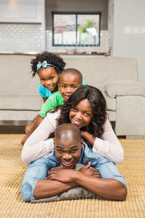 young boy: Happy family lying on the floor at home in the living room