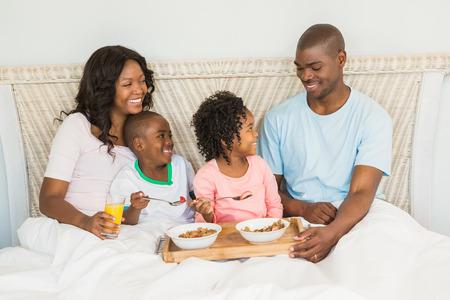 ni�os desayuno: La familia feliz desayunando juntos en la cama en la ma�ana