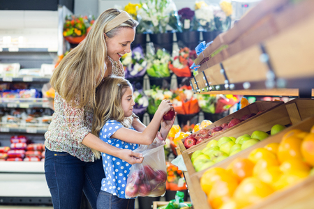 tienda de ropa: Joven madre con su hija en el supermercado Foto de archivo