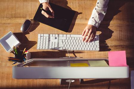 image recadrée de la femme en utilisant une tablette graphique dans son bureau