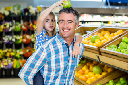 playing the market: Father giving his daughter a piggy back at supermarket Stock Photo