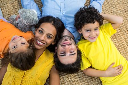 convivencia familiar: Familia sonriente que pone en la alfombra y mirando a la cámara