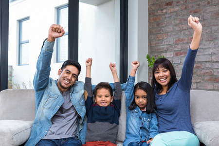 enjoyable: Happy young family watching tv in living room
