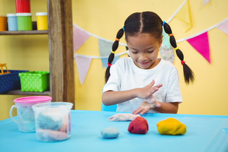 modelling clay: Happy girl rolling modelling clay in her hands Stock Photo