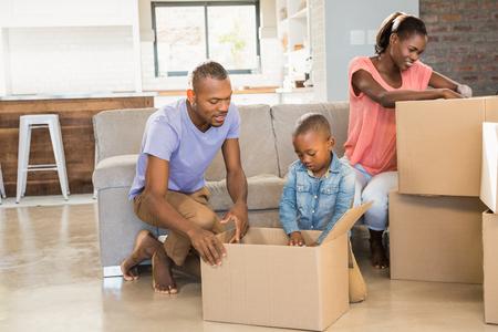 convivencia familiar: Familia desenvolviendo las cosas en la nueva casa en el salón Foto de archivo