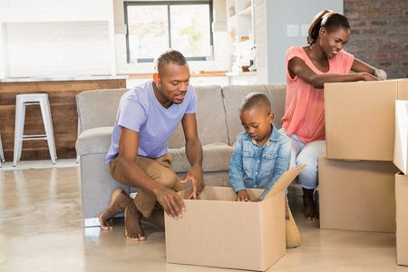 Family unwrapping things in new home in living room