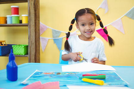 cut up: Smiling girl cut up some paper at the desk Stock Photo