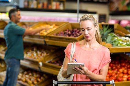 abarrotes: Mujer bonita que controla lista de la compra en el supermercado