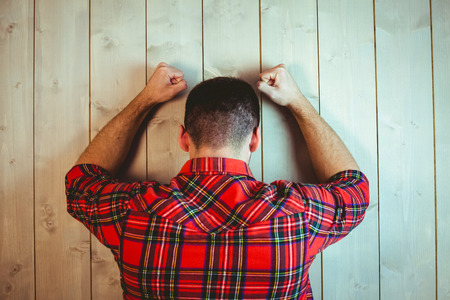 dreariness: Handsome hipster feeling stressed out on wooden background Stock Photo