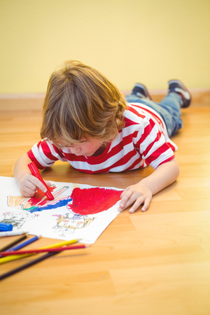 sitting on the ground: Boy lying on the ground colouring his picture Stock Photo