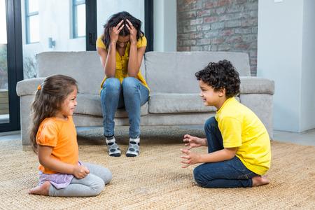 Marre mère écoutant ses jeunes enfants se battre à la maison dans le salon