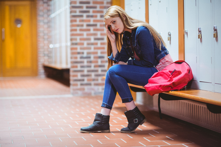 Worried student sitting in locker room and looking at the camera at the university