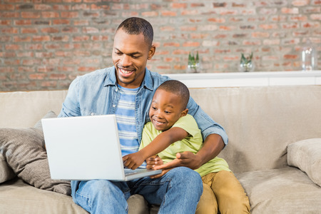 one family: Father and son using laptop on the couch in living room