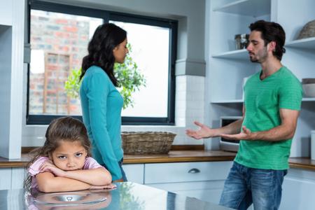 divorce: Niño triste escuchar argumentos a los padres en la cocina Foto de archivo