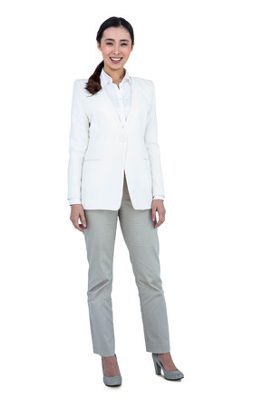 straight up: Smiling businesswoman standing straight up against white background Stock Photo