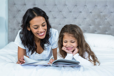family with one child: Happy mother and daughter reading a book on the bed at home Stock Photo