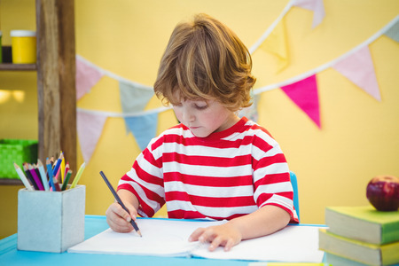 writing table: Boy using a pencil to write on paper at the desk Stock Photo