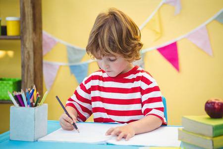 escritura: Muchacho que usa un lápiz para escribir en el papel en el mostrador
