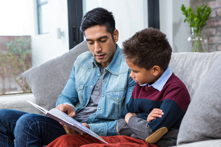 one family: Happy father reading book with his son in living room Stock Photo