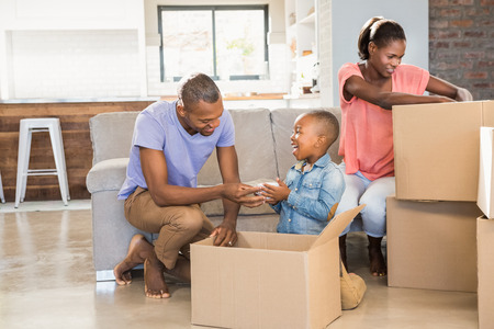 living things: Family unwrapping things in new home in living room