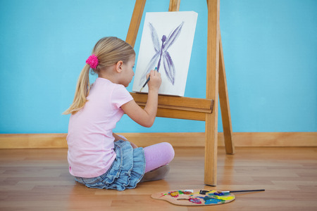 girl sitting down: Girl sitting down painting a picture on an easel