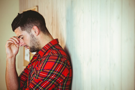 Handsome hipster feeling stressed out on wooden background 스톡 콘텐츠